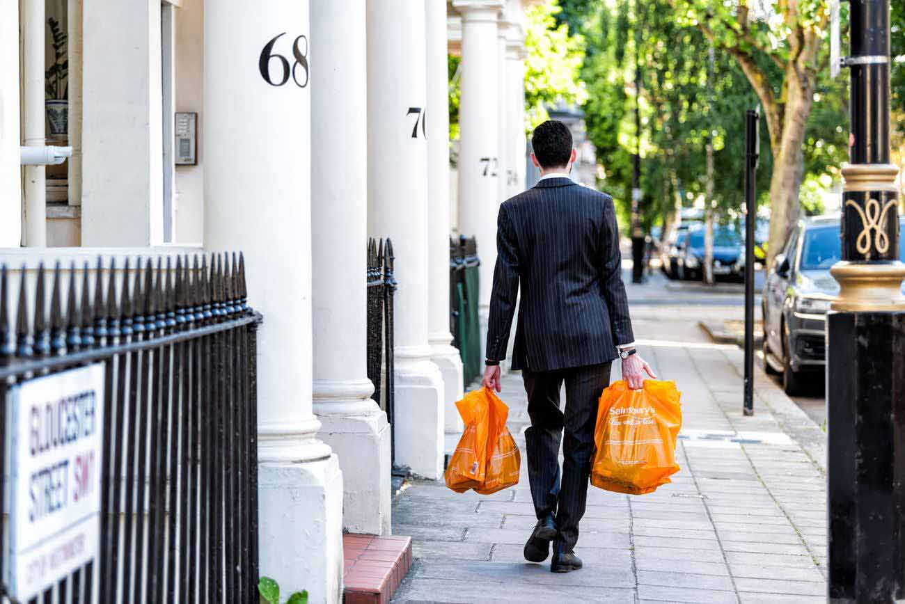 Man in suit walking past houses carrying Sainsburys shopping bags